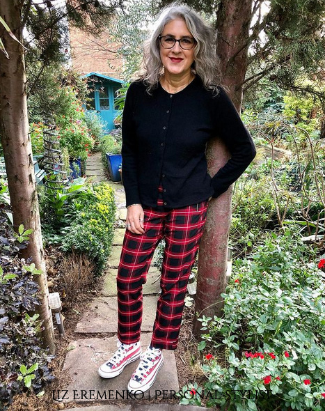 Image of LIz in red and black tartan trousers with black sweater