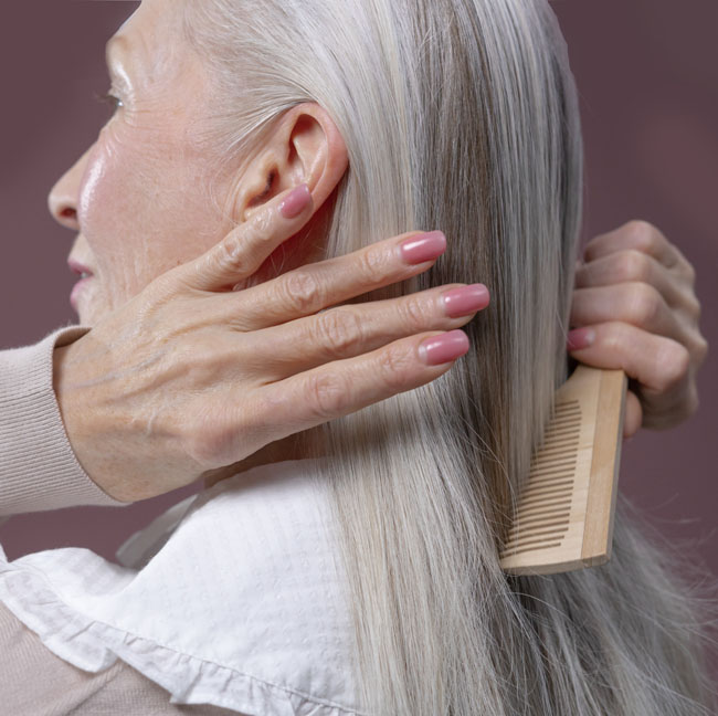 Image of silver hair woman combing her hair