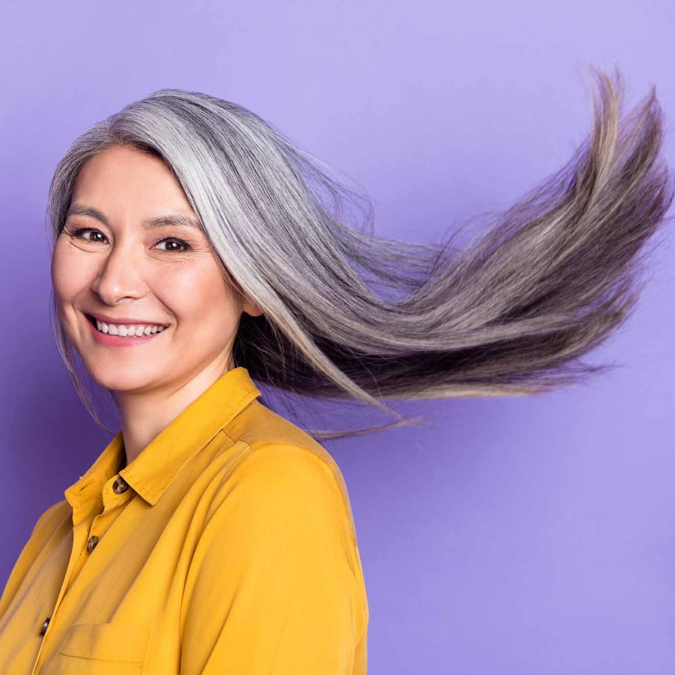 Gray hair woman hair flying isolated over bright violet purple color background.